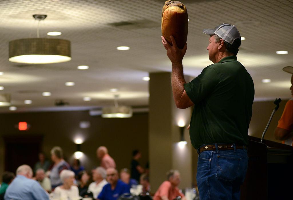 Stanley Lynn presents a ham during the 75th Annual Ham Auction