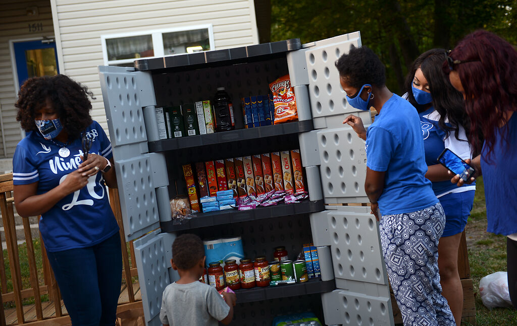 From left, Martha Tomlin-McCrary, Jamison Malveaux, 3, LeAnn Stroupe, Shannon Fennell and Khandicia Randolph look through the blessing box to show the community what it contains
