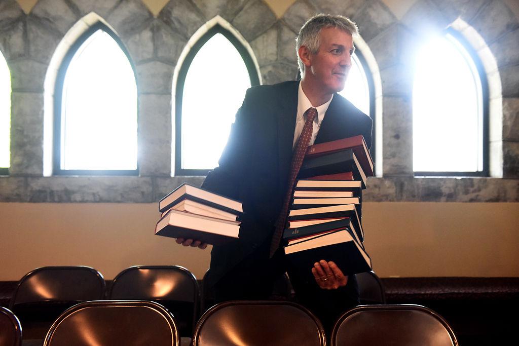 David Schenker picks up bibles after the memorial service