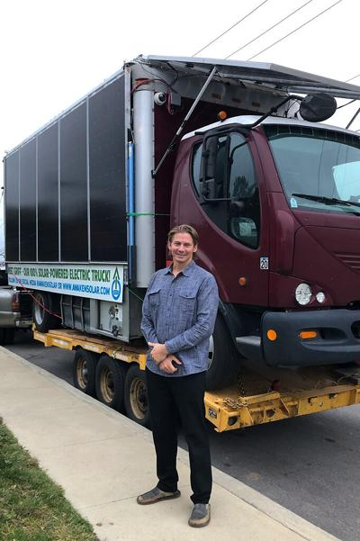 """Joshua """"Sunshine"""" Hill stands in front of a solar-powered electric truck"""