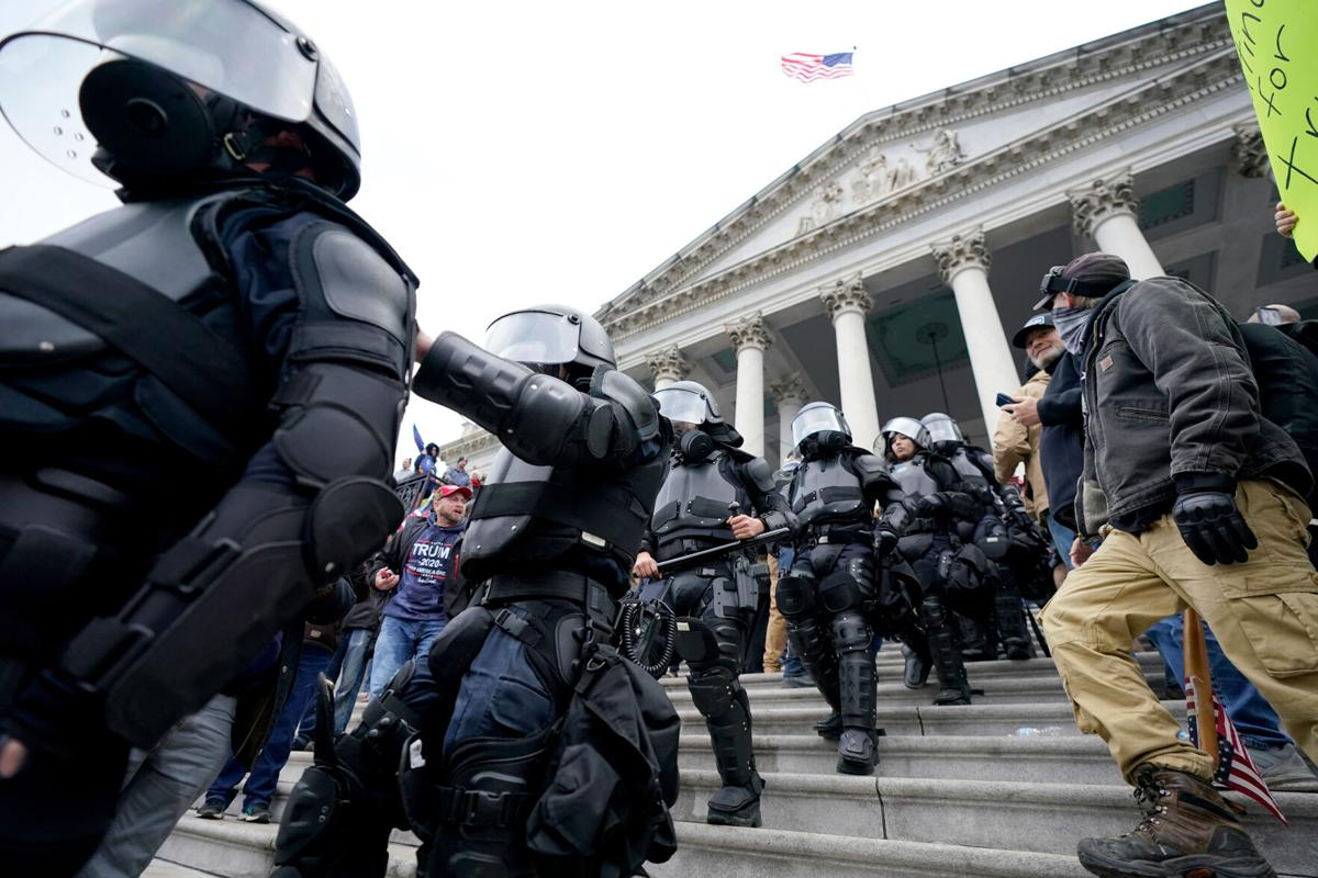 Police in riot gear walk out of the Capitol