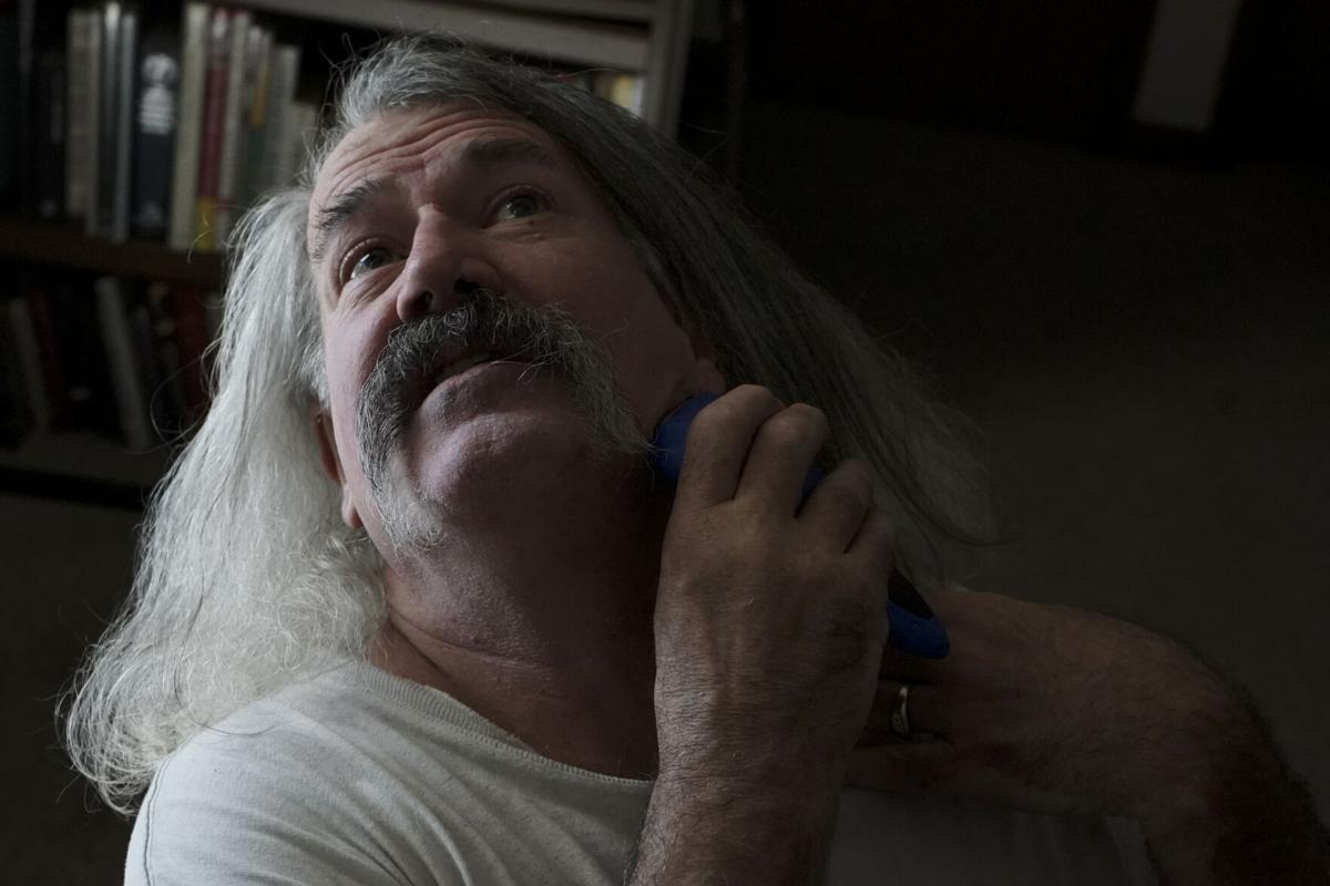 Robert Morrison shaves at his desk before leaving his home