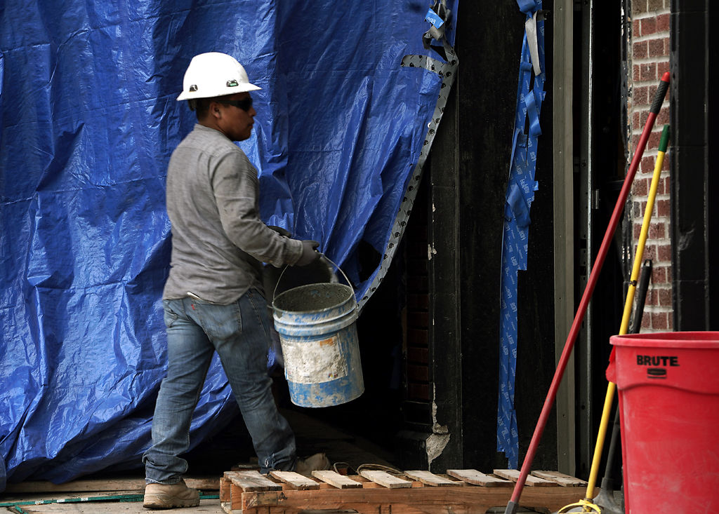 A construction worker carries a bucket Thursday at Dungarees