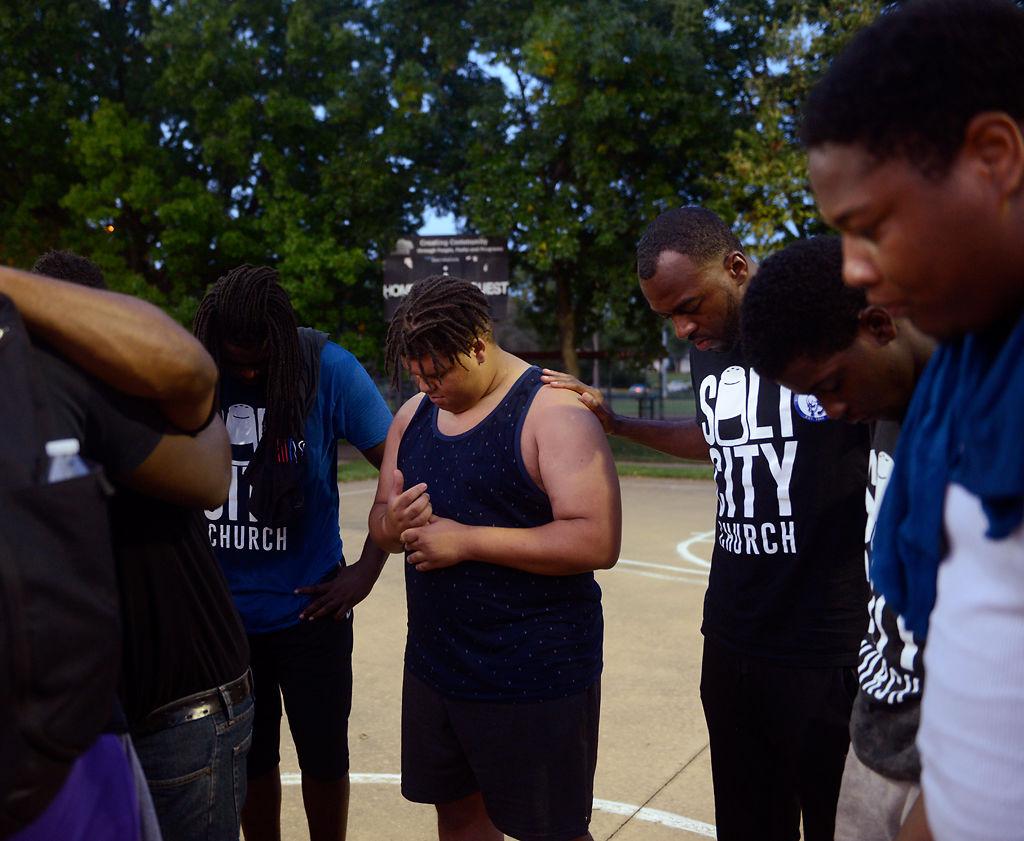 Chris Carter, center, bows his head in prayer