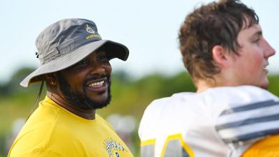 Battle High School head football coach Atiyyah Ellison smiles while talking with senior Landon Ray