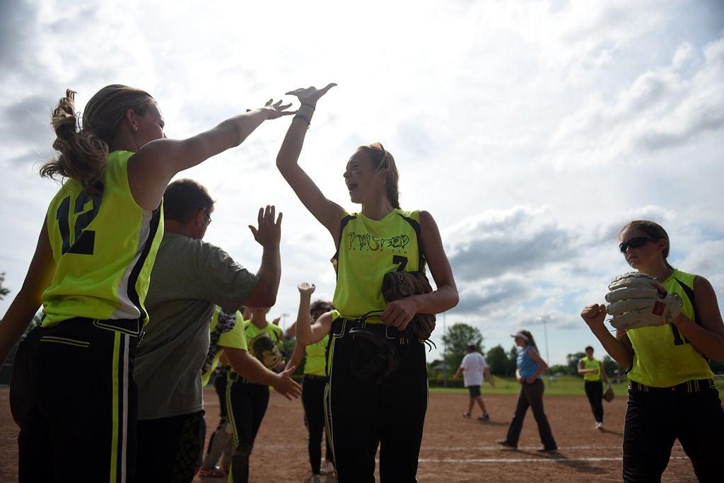 Olivia Wood, 15, center, celebrates with her teammates