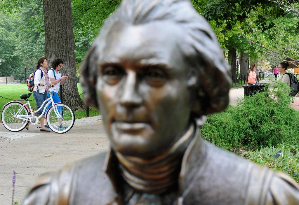 Students walk past a statue of Thomas Jefferson along MU's Francis Quadrangle