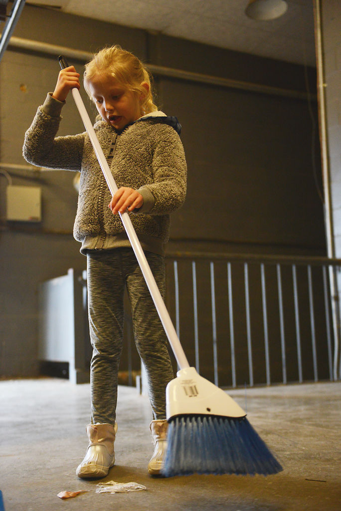 Charlotte Knudsen, 6, sweeps remains of produce