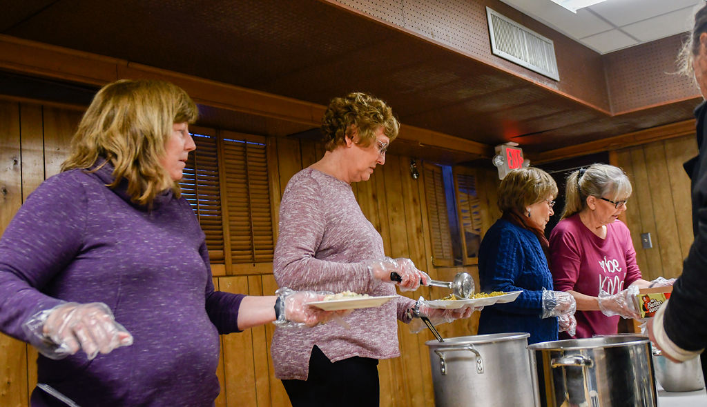 Volunteers serve meals for the homeless