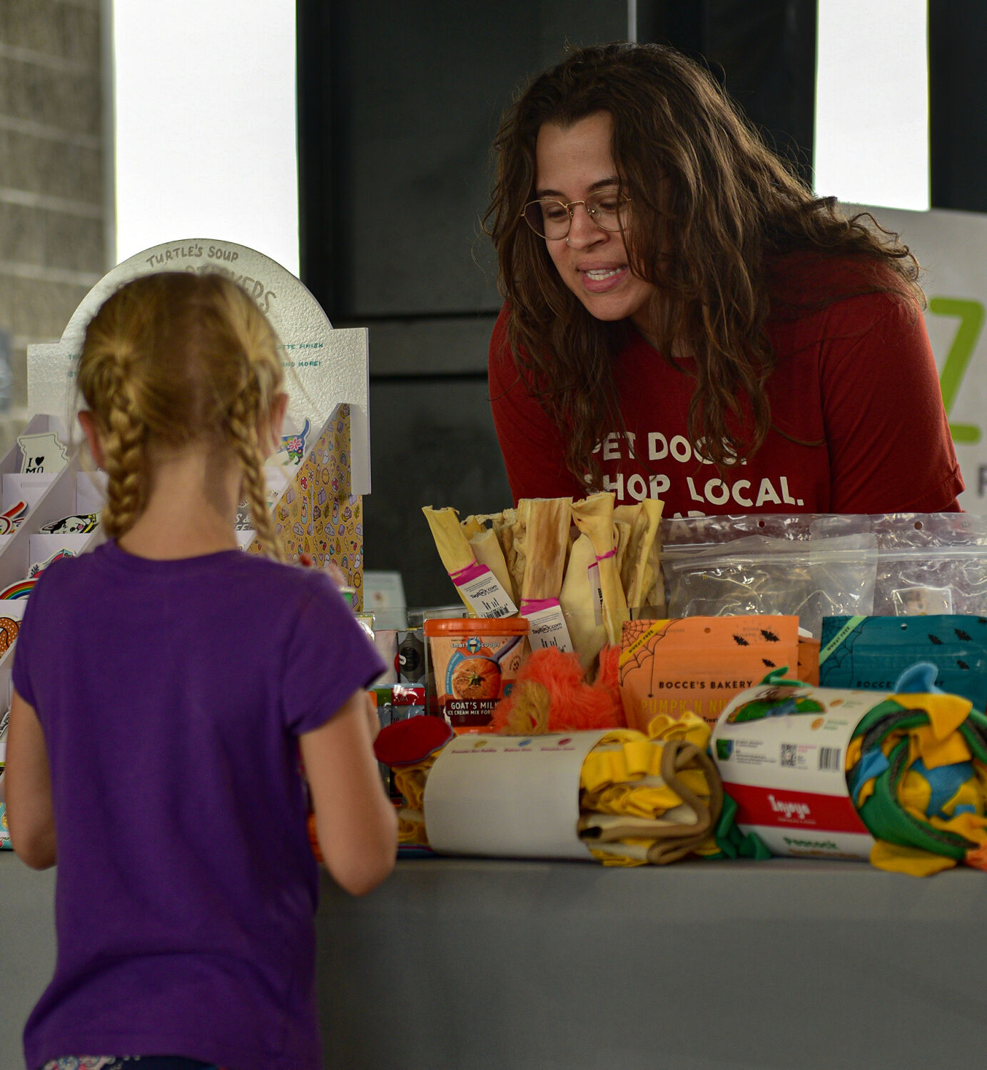 Left, Ellie Quick 6, talks with employee Kayleigh Kruckman, at the Lizzi & Rocco's Holistic pet store booth