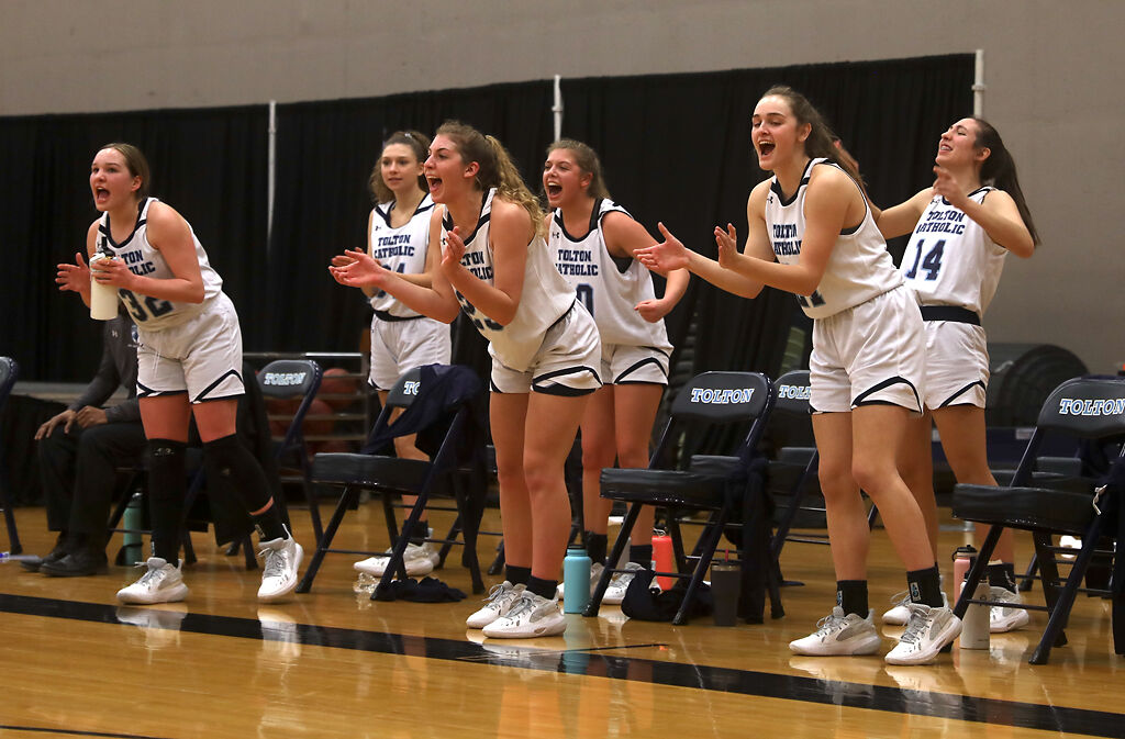 Players from Tolton High School cheer after a teammate makes a basket