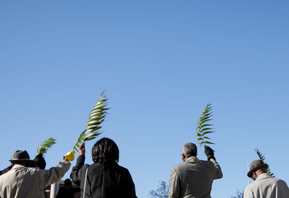 Members of the Second Missionary Baptist Church raise their palm fronds