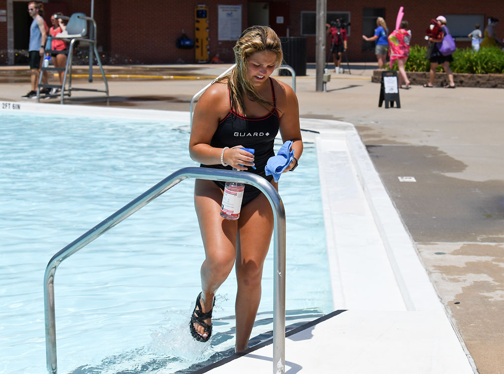 McKenna Asmus disinfects a hand rail between swimming sessions