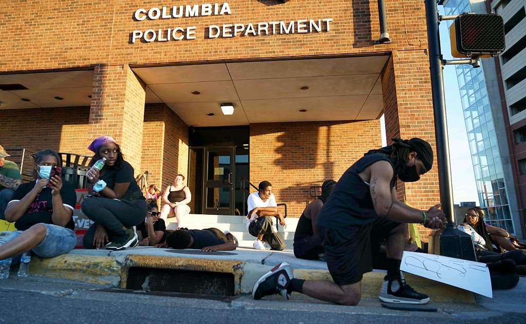 Protesters kneel outside the Columbia Police Department