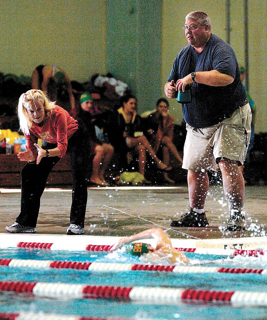 Linda, left, and John Hamilton cheer on a Rock Bridge swimmer together