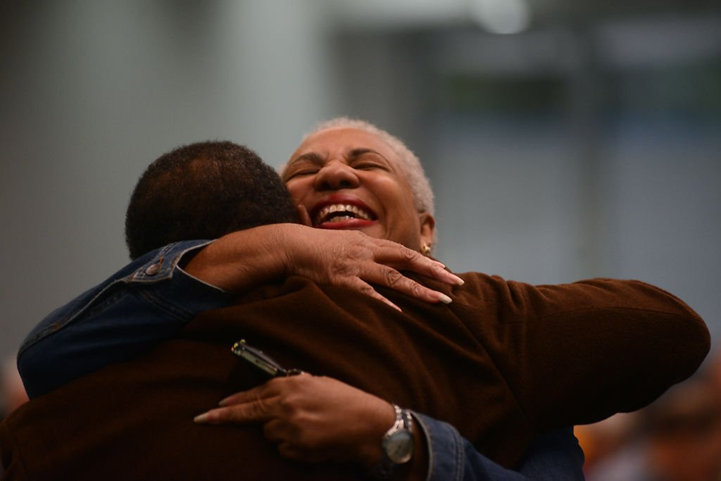 Marie Glaze hugs her friend Ronald Williams at the segregation lecture series