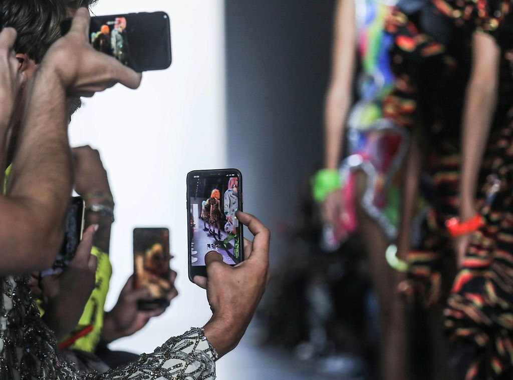 Guests grab cellphone photos of models showcasing the latest fashion