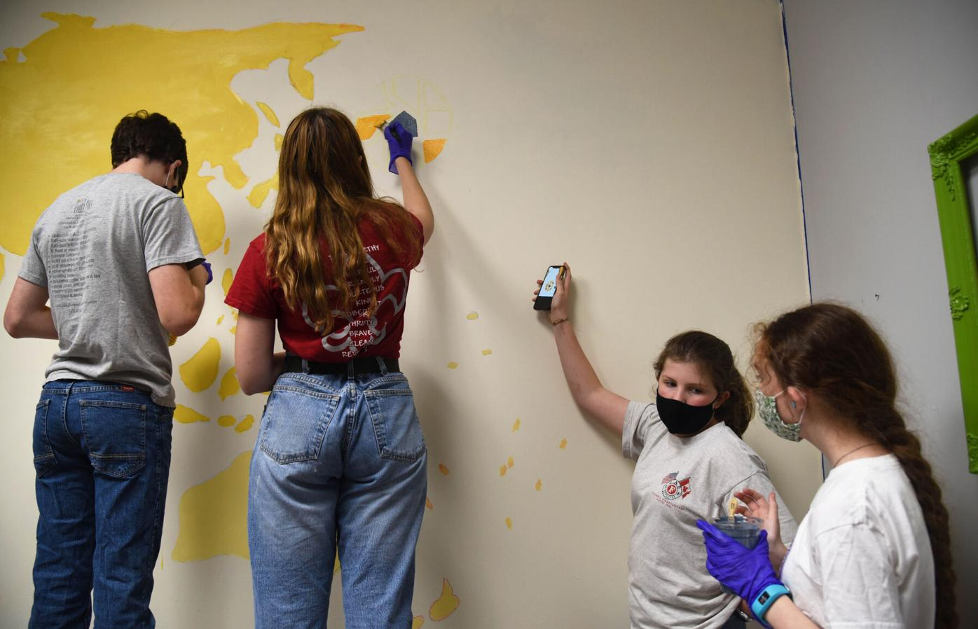 Miles Schroeder, Sophie Froese, Elizabeth Odette and Erica Schroeder assist in painting