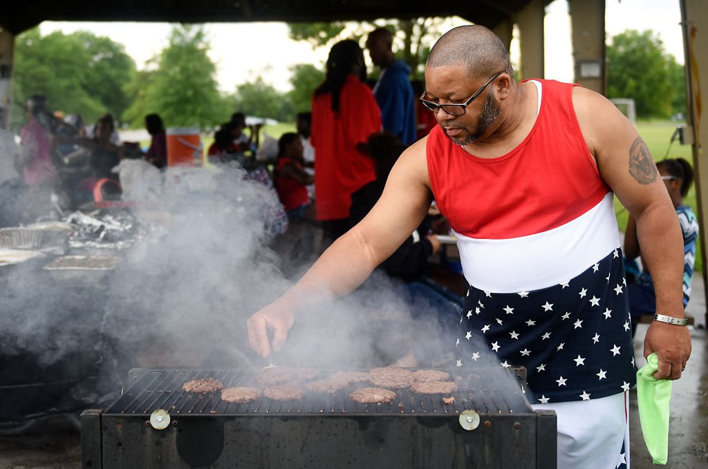 Ronald Sanders flips burgers on one of the three grills running the Hall family reunion