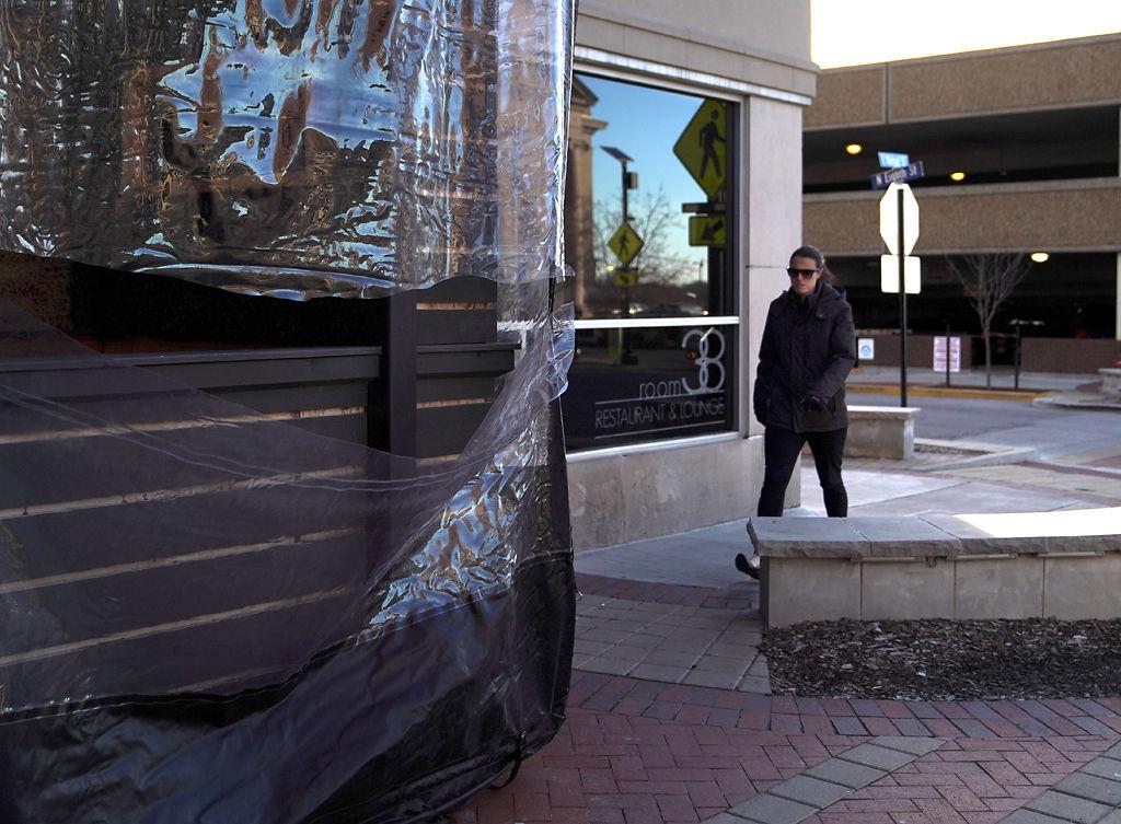 Morgan Casui walks on the sidewalk between Room 38 Restaurant and Lounge and East Walnut Street