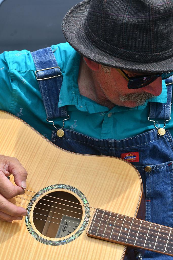 Lyle Burton tunes his guitar before performing