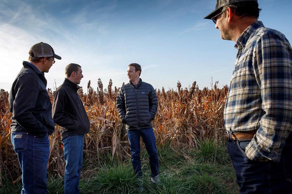 Mark Zuckerberg walks next to a field with Dustin and Austin Stanton