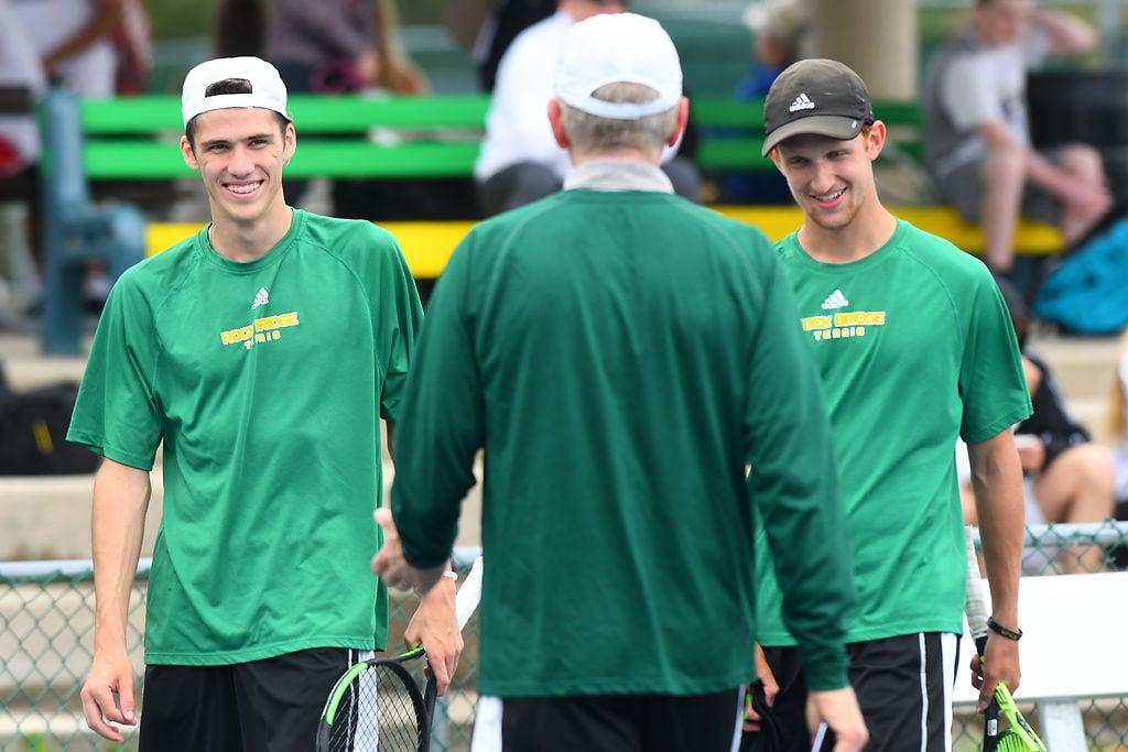 Rock Bridge tennis players Jake Fraunfelder, left, and Zach Grueber high five Rock Bridge head coach Ben Loeb