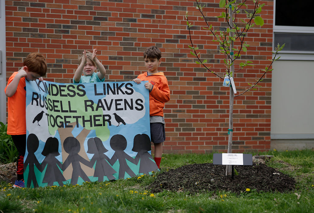 "Kindergarteners Jace Stafford, Colton Moll and Fionn Torres hold a sign during the dedication of a ""kindness tree"""