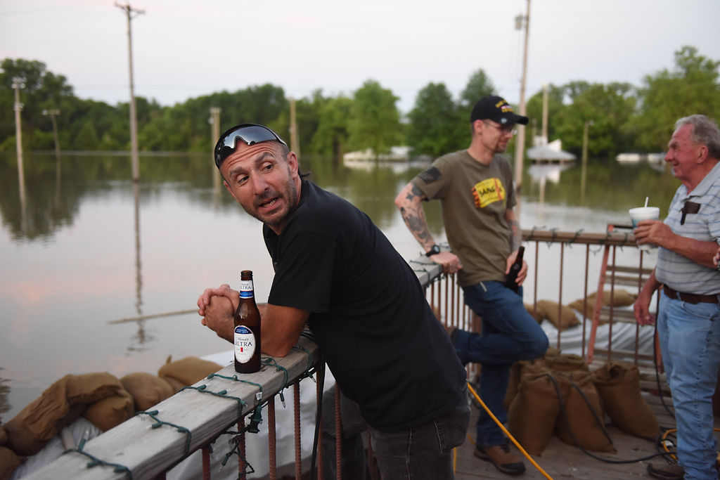 Danny Lamons drinks a beer with friends and community members after checking water pumps