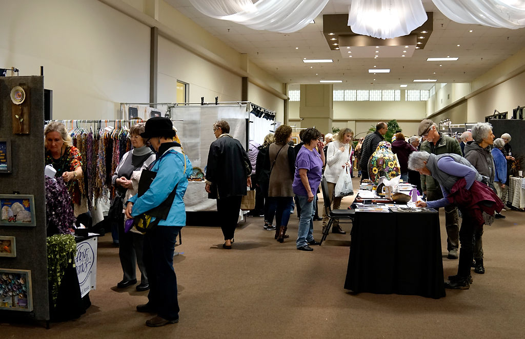 Attendees of the Fall Into Art Show looks at artwork by various artists