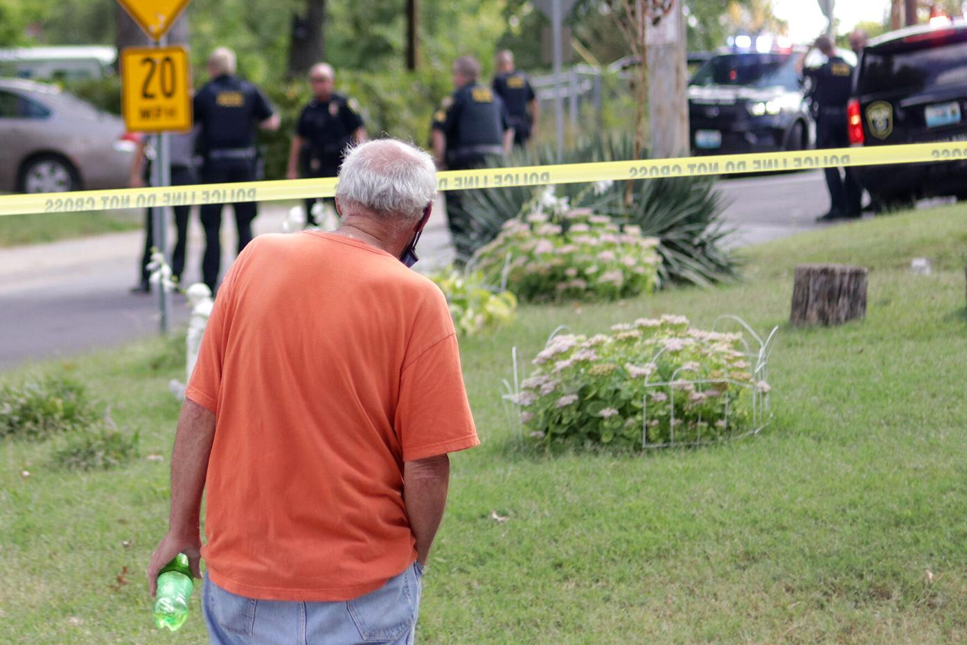 A bystander watches police officers work the scene of a shooting