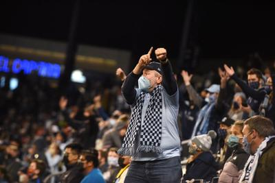 A fan points to his wrist and yells at a referee (copy)