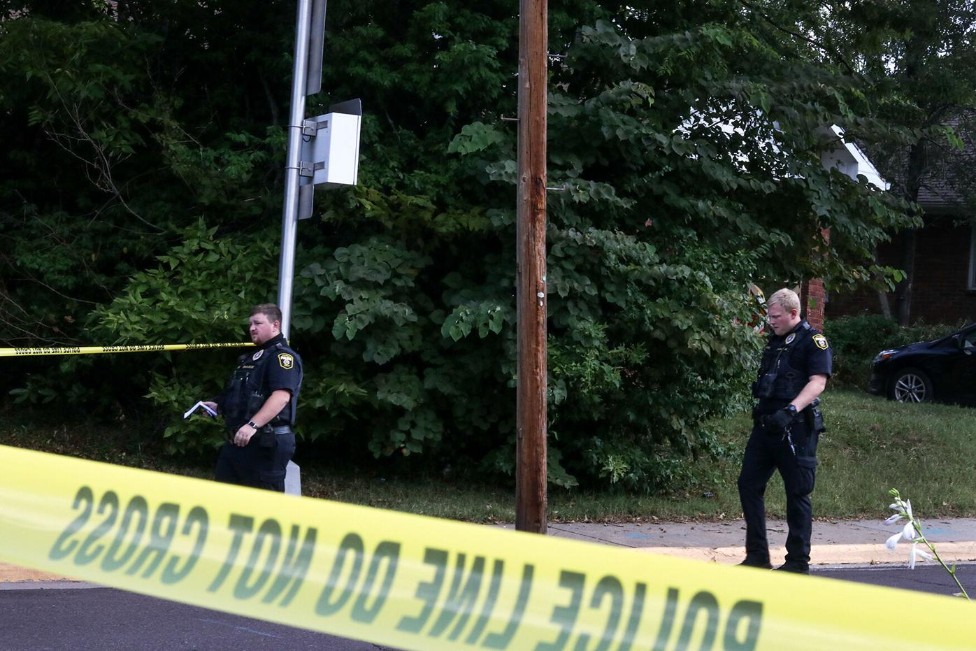 Police officers walk through a taped-off area