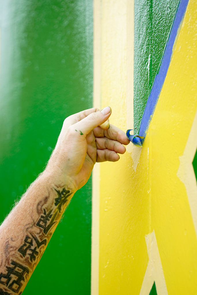 Michael Allegri removes tape from the caboose being painted