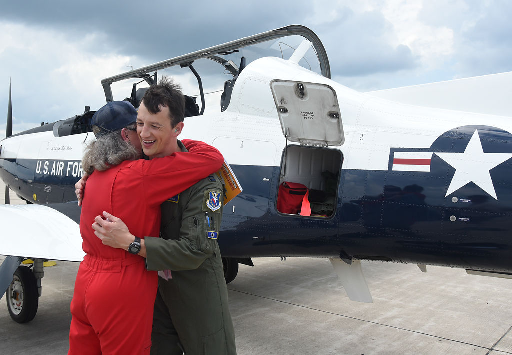 Mary McCleary Posner gives Captain Marc A. Daigle a metal and a hug
