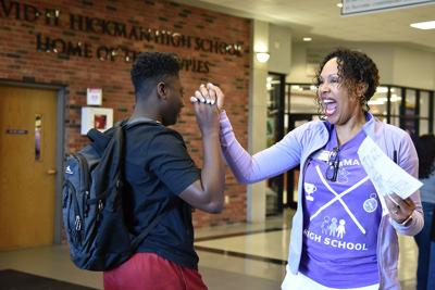 Cassandra Walker Suggs high-fives a student as they enter Hickman High