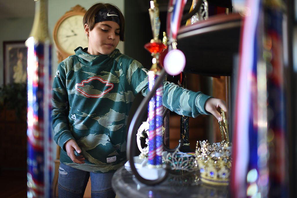 Wyatt Bonaparte, 12, shows off his wall of title trophies