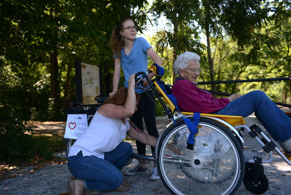 Heather Marriott adjusts the Duet tandem wheelchair bicycle while Veronica Fritz holds onto it