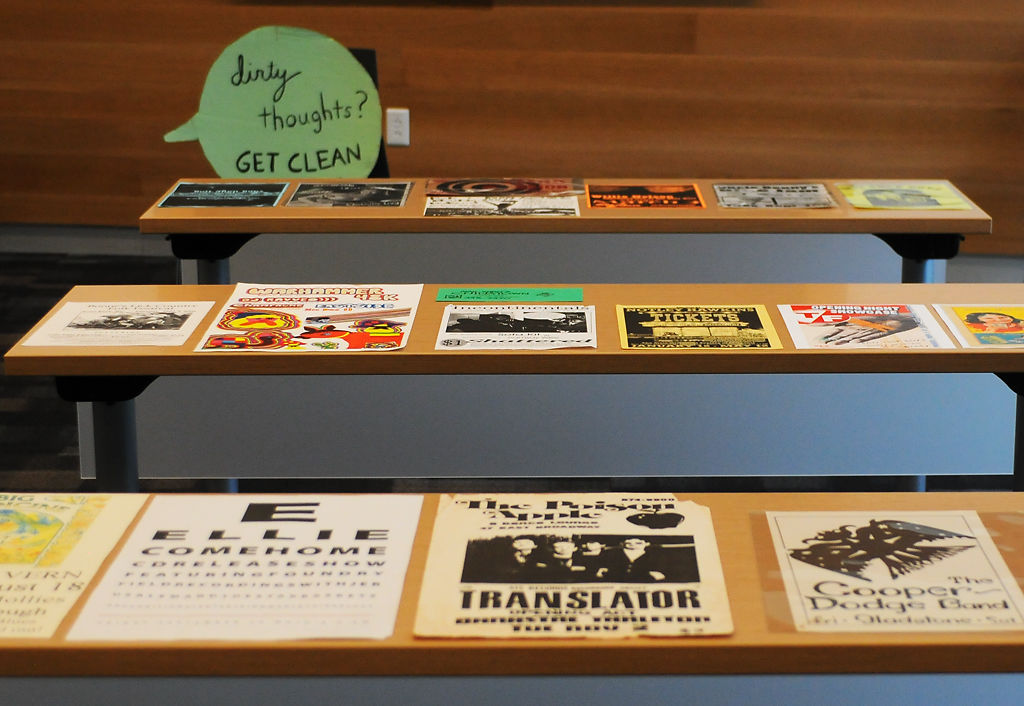Posters from different concerts hosted in Columbia through the years lay on tables