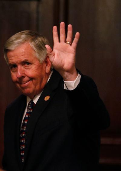 Mike Parson waves to the media