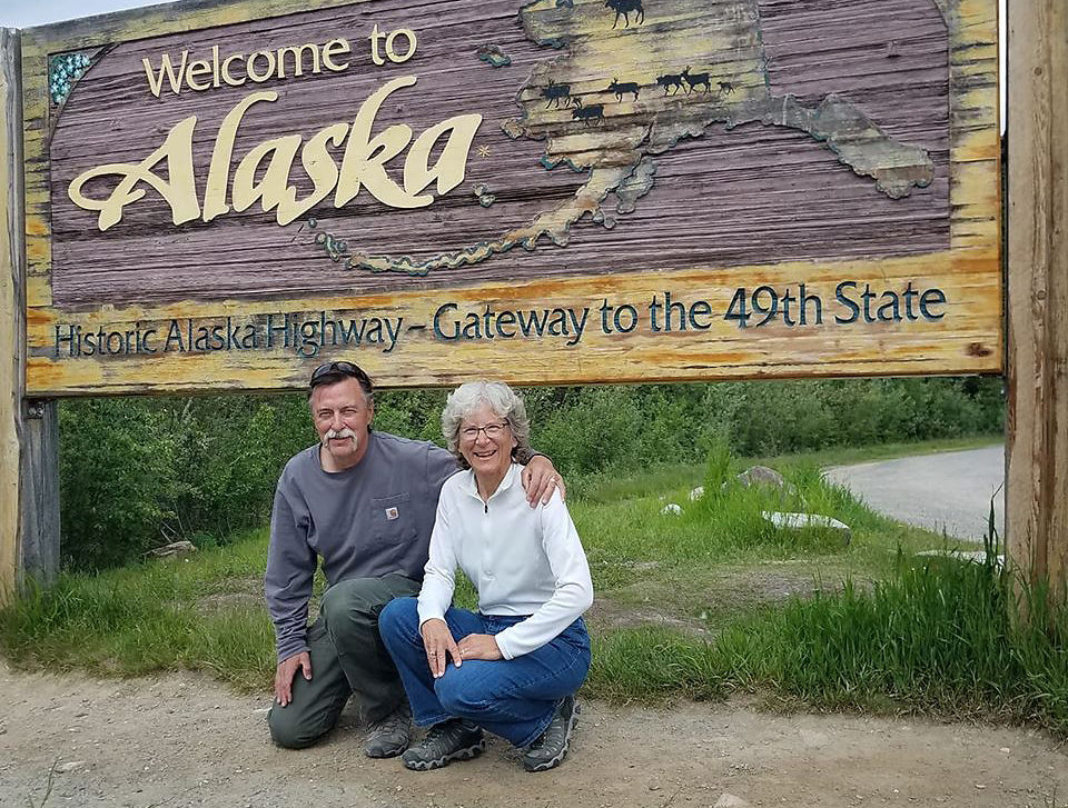"""Rochelle Renken and Michael Huffman in front of a """"Welcome to Alaska"""" sign"""