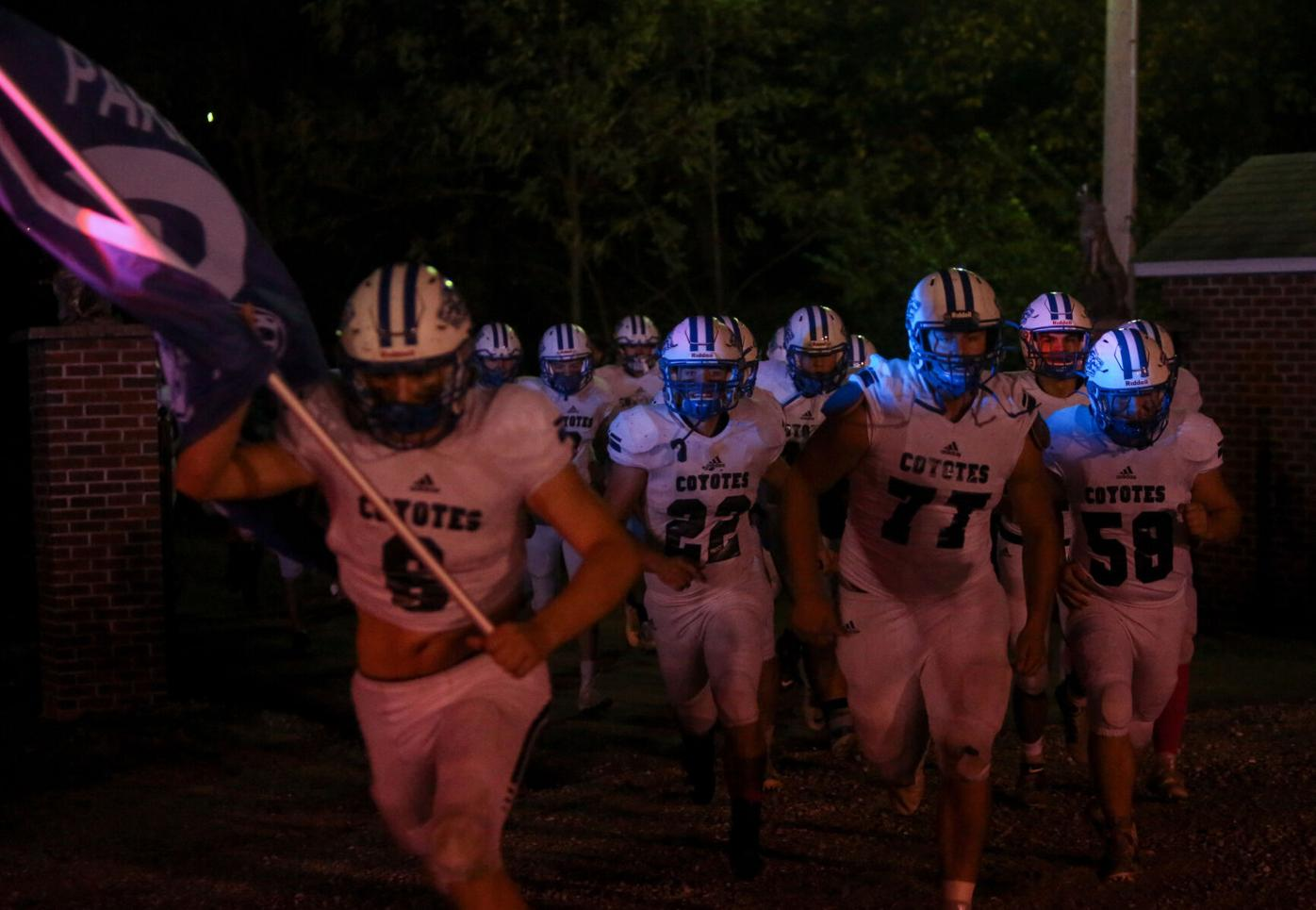 The Paris High School football team runs onto Warbritton Field