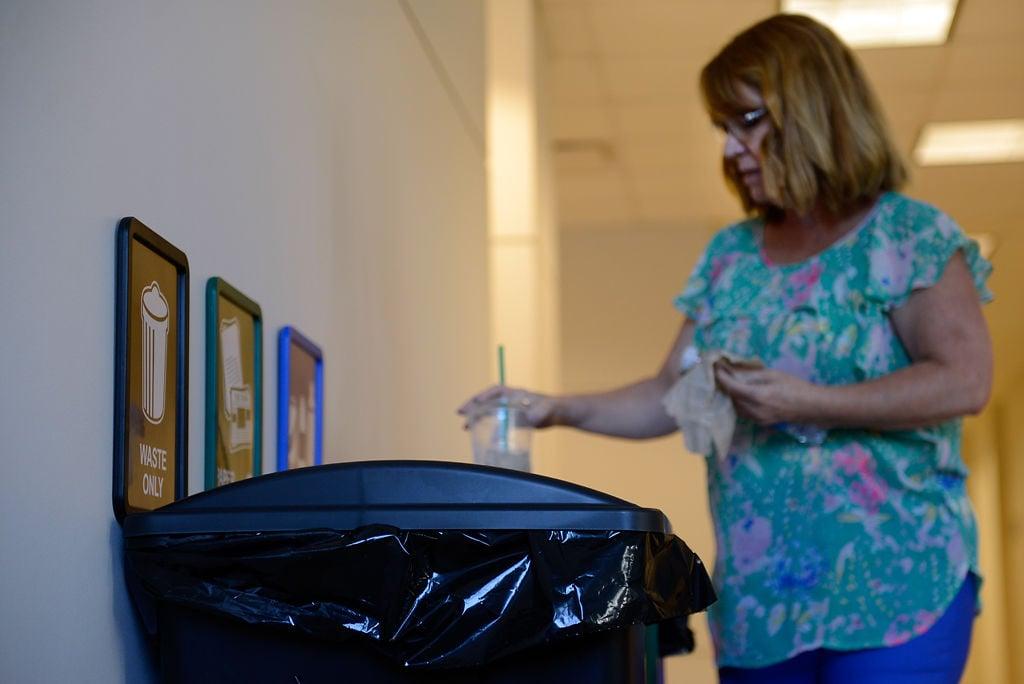 Jody Baker drops a plastic cup into a recycling bin
