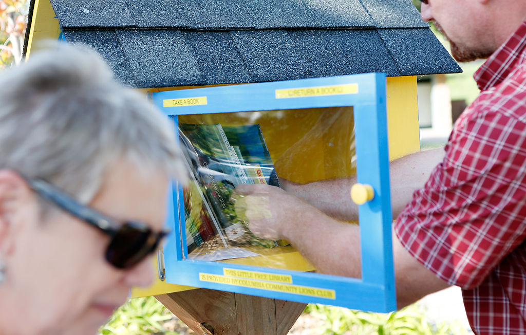 Mike Anderson adds books to the Stephens Lake Park little library