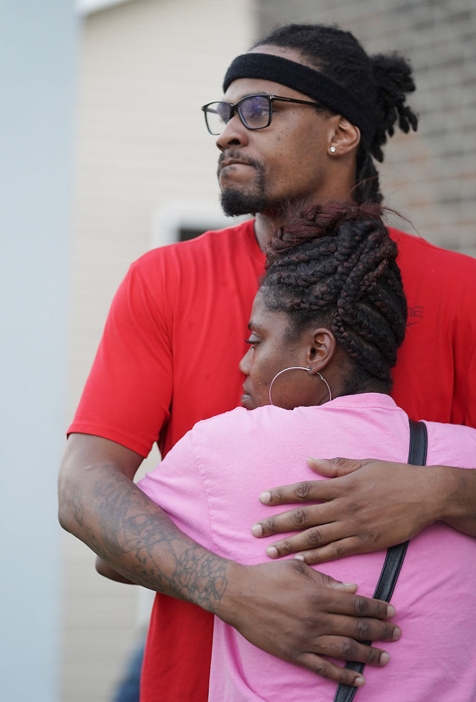 Terrance Williams embraces Maleshia Estes at the scene of a shooting at 720 Demaret Drive