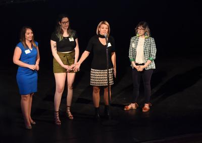 Sarah Hill, center, stands