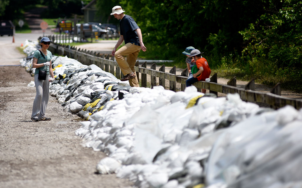 Jon Klaas scales a sandbag mound with his wife, his son and his daughter