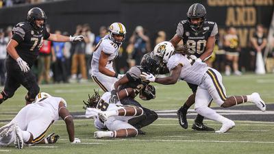 Vanderbilt freshman running back Keyon Brooks is tackled by Missouri linebackers Jatorian Hansford and Nick Bolton