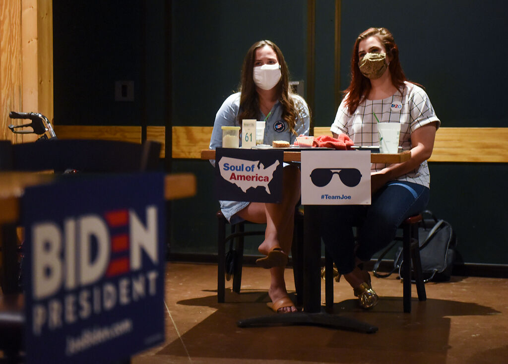 Tori Schafer, left, and Taylor Tutin keep their eyes trained on the television as Joe Biden speaks