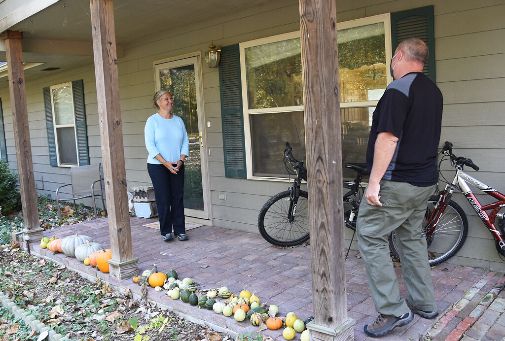 Adrian Plank, right, knocks on resident Julie Mitchell's door as a part of his preparation for the election on Saturday in Columbia.